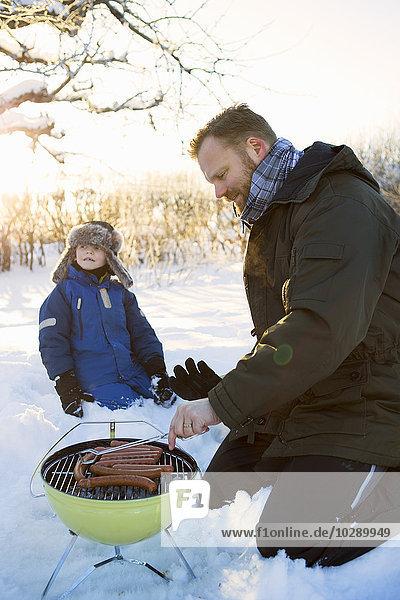 Sweden  Stockholm  Alvsjo  Father preparing food with son (4-5)
