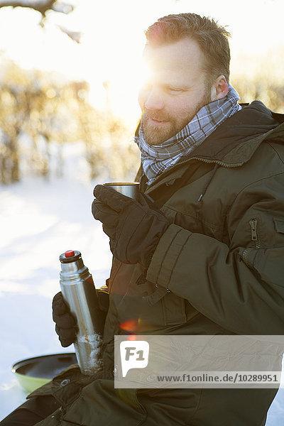 Sweden  Stockholm  Alvsjo  Man drinking from flask