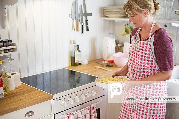 Sweden  Stockholm Archipelago  Grasko  Woman preparing bilberry pie for baking