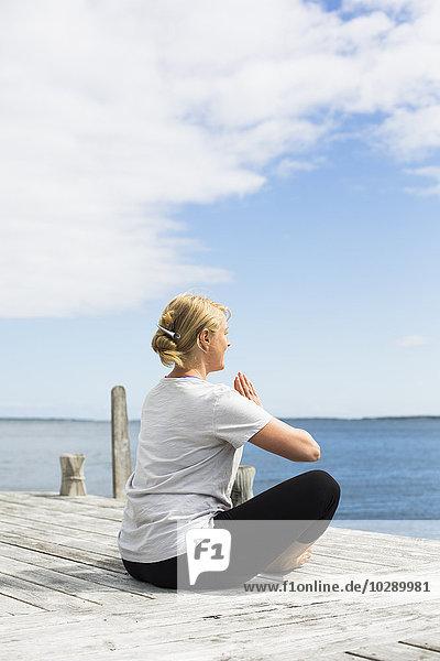 Sweden  Stockholm Archipelago  Grasko  Woman doing yoga on jetty