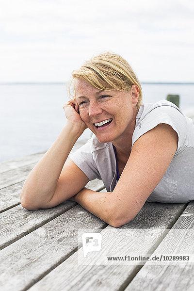 Sweden  Stockholm Archipelago  Grasko  Woman lying on jetty