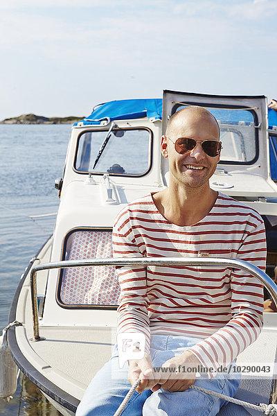 Schweden  Vastra Gotaland  Göteborg Archipel  Styrso  Mann mit Seil auf der Yacht