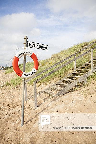 Schweden  Skane  Angelholm  Holztreppe und Rettungsring am Strand
