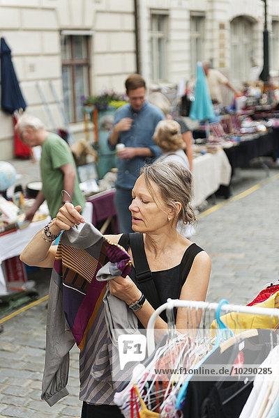 Sweden  Stockholm  Normalm  Blasieholmstorg  Portrait of mature woman choosing dress at flea market