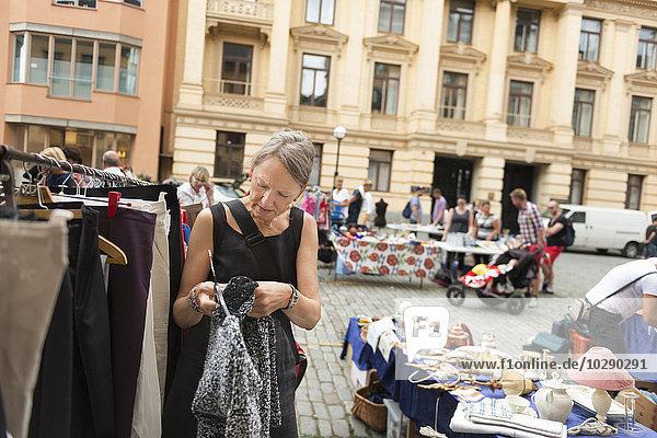 Schweden  Stockholm  Normalm  Blasieholmstorg  Porträt einer reifen Frau  die sich auf dem Flohmarkt kleidet. Schweden, Stockholm, Normalm, Blasieholmstorg, Porträt einer reifen Frau, die sich auf dem Flohmarkt kleidet.