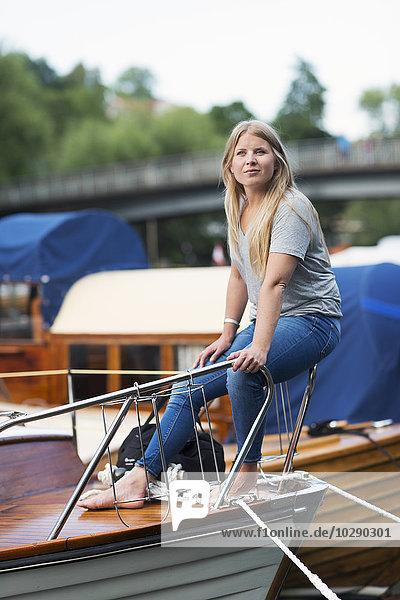 Schweden  Stockholm  Sodermalm  Porträt einer Frau  die auf dem Geländer des Bootsbogens sitzt