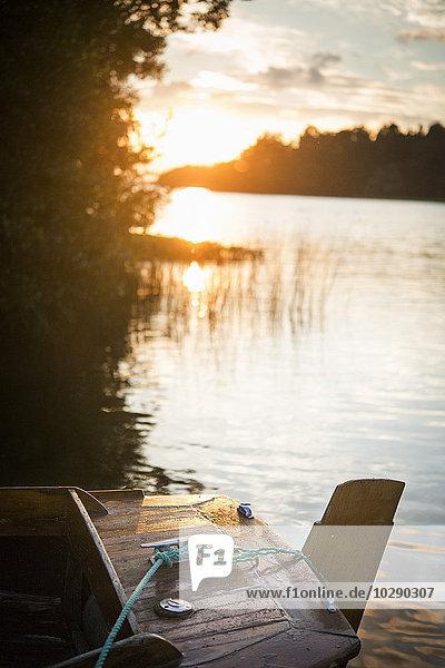 Schweden  Uppland  Ekero  Rastaholm  Holzboot bei Sonnenuntergang auf dem Fluss vertäut