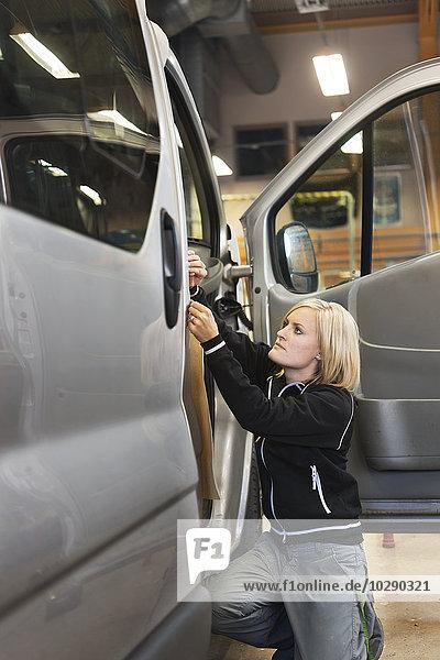Schweden  Frau bei der Arbeit am Auto in der Werkstatt