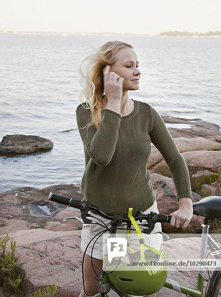 Finnland  Helsinki  Portrait einer jungen Frau mit Fahrrad auf dem Meer