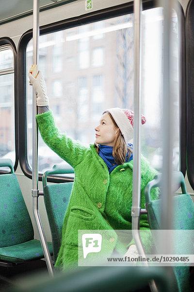 Finnland  Helsinki  Junge Frau beim Drücken der Taste zum Anhalten in der Straßenbahn