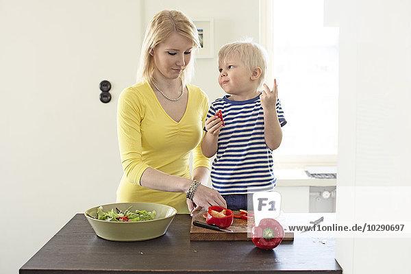Finland  Helsinki  Kallio  Mother and son making salad in kitchen