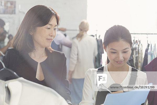Modedesignerin beobachtet Assistentin beim Notieren