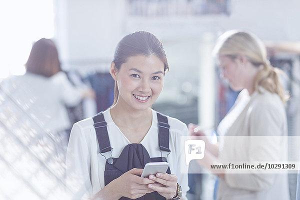Porträt selbstbewusste Modedesignerin SMS mit Handy