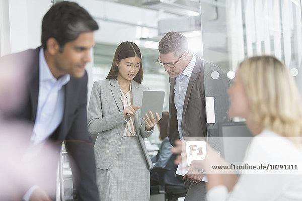Geschäftsleute teilen sich ein digitales Tablett im Konferenzraum