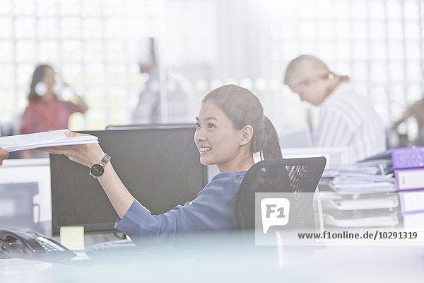 Lächelnde Geschäftsfrau mit Papierkram am Schreibtisch im Büro