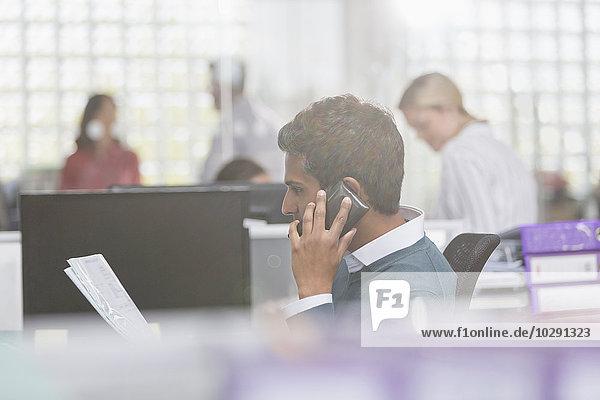 Geschäftsmann mit Papierkram am Handy im Büro