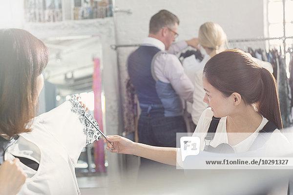 Modedesigner untersuchen Kleidung im Büro
