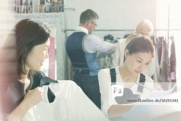Modedesigner machen sich Notizen zur Kleidung