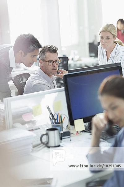 Geschäftsleute  die am Computer im Büro arbeiten