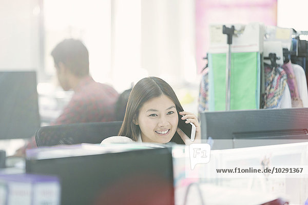 Lächelnde Modedesignerin beim Telefonieren am Schreibtisch im Büro