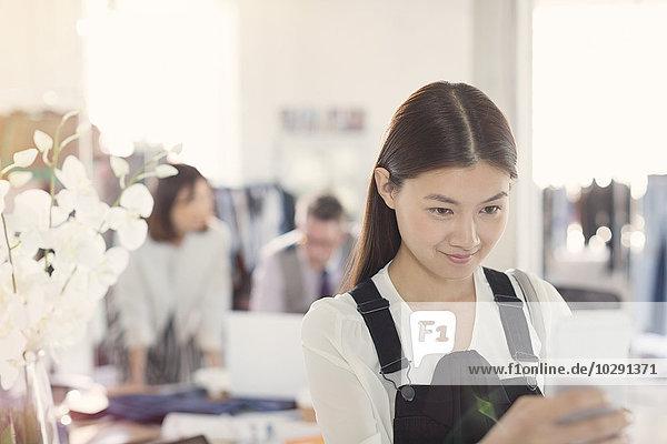 Lächelnder Modedesigner texten mit Handy
