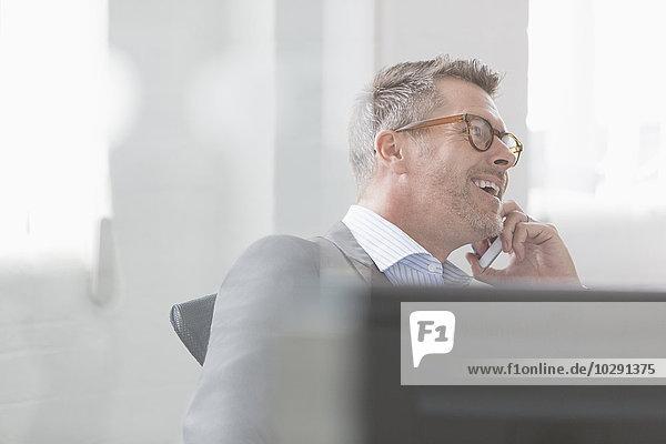 Lächelnder Geschäftsmann im Gespräch mit dem Handy