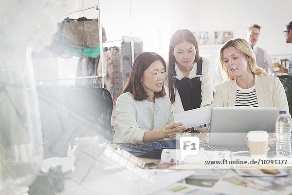 Modedesigner diskutieren Papierkram am Laptop im Büro
