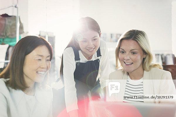Lächelnde Modedesigner arbeiten am Laptop im Büro