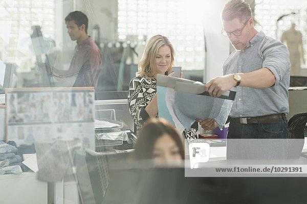Modedesigner untersuchen Stoff im Büro
