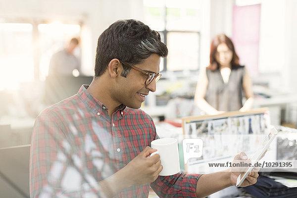 Modedesignerin mit digitalem Tablett und Kaffeetrinken im Büro