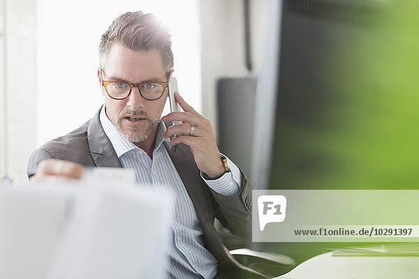 Geschäftsmann bei der Untersuchung von Papierkram am Handy im Büro