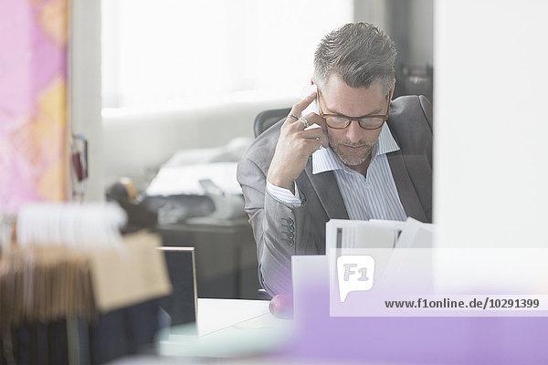 Fokussierter Geschäftsmann  der den Papierkram am Schreibtisch im Büro überprüft.