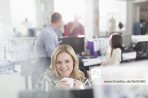 Portrait lächelnder Modedesigner beim Kaffeetrinken am Computer im Büro