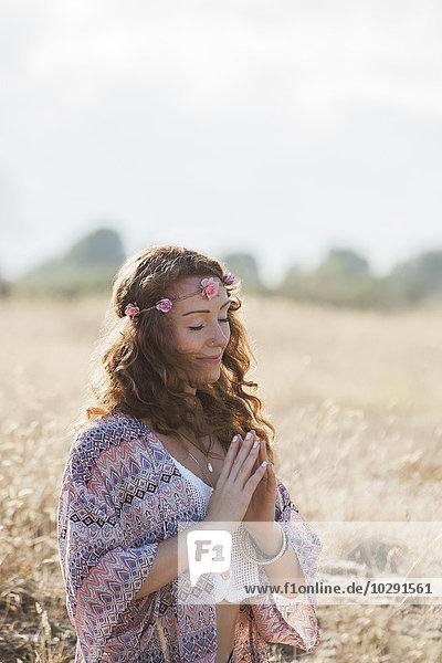 Serene boho Frau meditiert mit den Händen in der Mitte des Herzens in einem sonnigen ländlichen Gebiet.