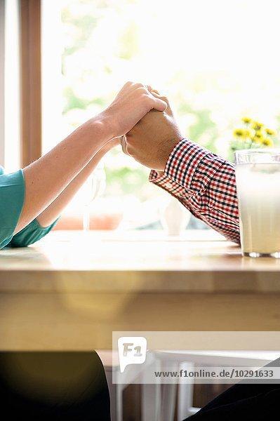 Beschnittene Seitenansicht des Paares  das die Hände über dem Tisch hält.
