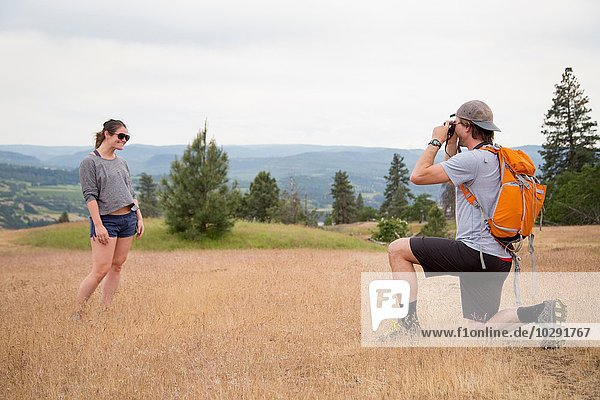 Junger Mann fotografiert junge Frau in ländlicher Umgebung