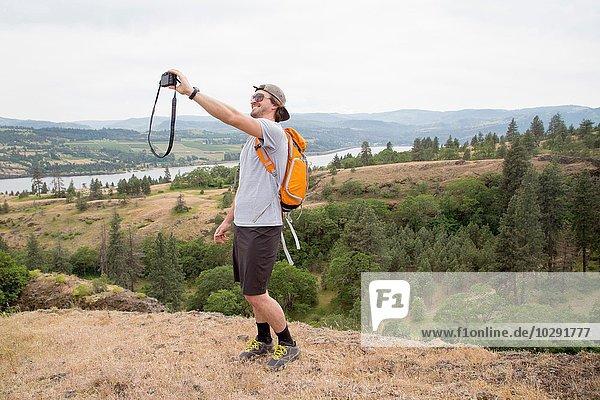 Junger Mann  auf dem Berg stehend  Selbstporträt mit Kamera aufnehmend
