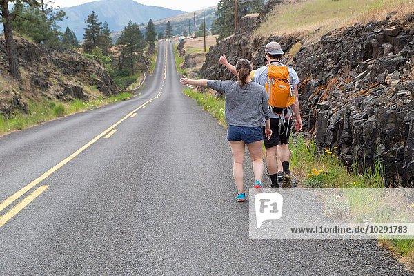 Junges Ehepaar beim Wandern entlang der Straße  beim Versuch  den Daumen zu heben  Rückansicht