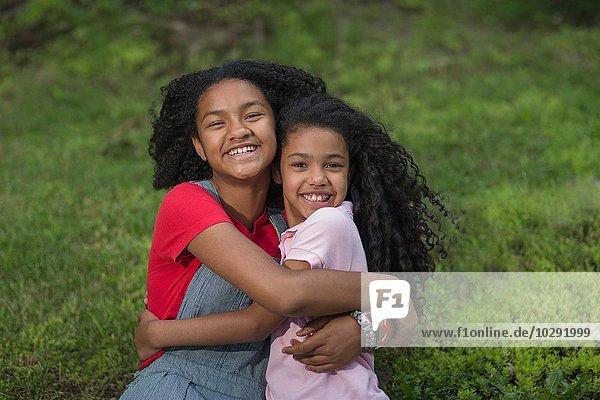 Portrait of girls hugging looking at camera smiling