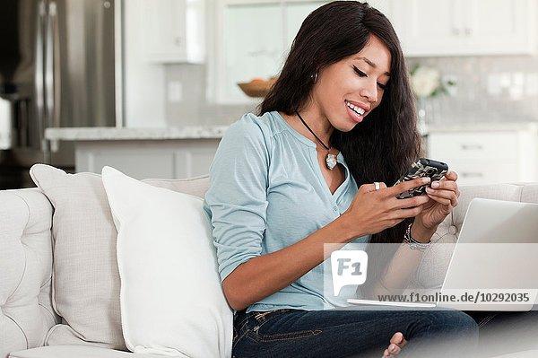 Junge Frau  entspannt auf dem Sofa  Laptop auf dem Schoß  Smartphone haltend