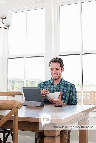 Mittlerer Erwachsener Mann beim Frühstücken  während er sich die digitale Tafel ansieht.