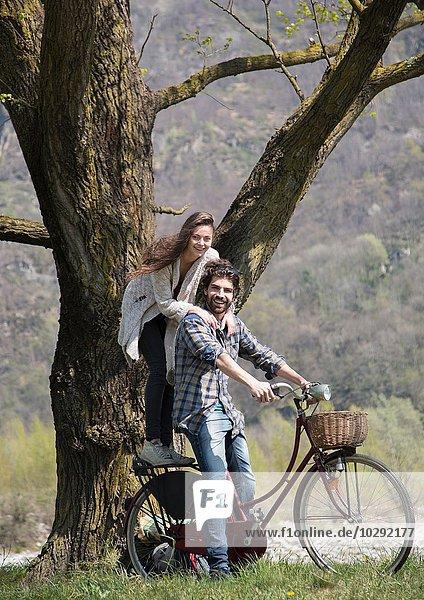 Portrait eines jungen Paares auf dem Fahrrad am Baum