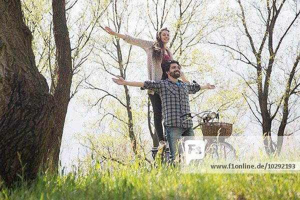 Junges Paar auf dem Fahrrad mit offenen Armen im ländlichen Wald