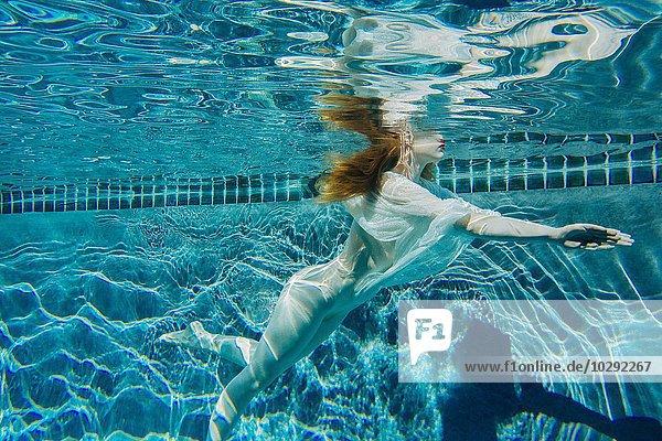 Junge Frau  die unter Wasser schwimmt und ein dünnes weißes Hemd trägt.