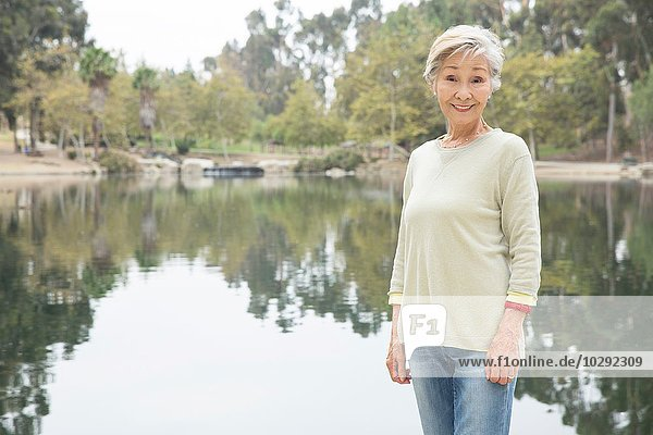 Porträt einer älteren Frau am See stehend