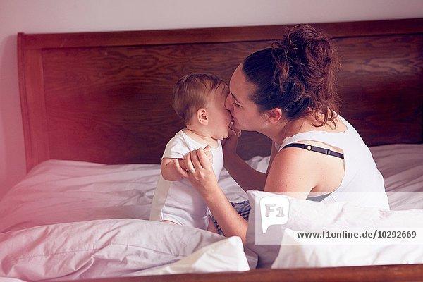 Mutter und Kind spielen auf dem Bett