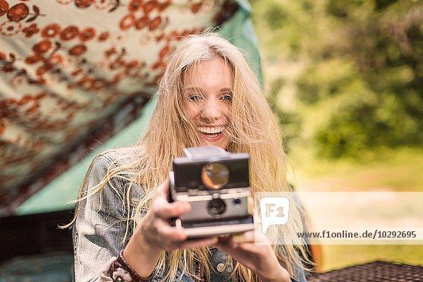 Porträt einer jungen Frau beim Fotografieren mit Sofortbildkamera beim Zelten