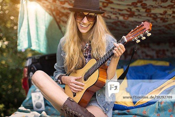 Porträt einer jungen Frau  die beim Zelten im Stiefel die Ukulelele spielt.