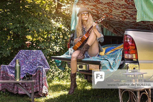 Junge Frau spielt Ukulelele beim Zelten im Pick-Up-Stiefel