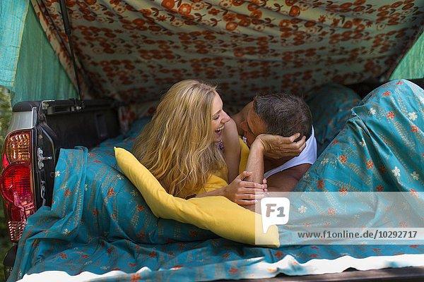 Erwachsener Mann und Freundin liegend im Stiefel beim Zelten